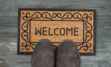 Welcome cleaning foot carpet with shoes and shoe print on it. Stok Fotoğraf