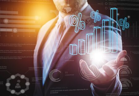 Unrecognizable businessman holding bar chart hologram. Infographics interface foreground. Toned image double exposure.