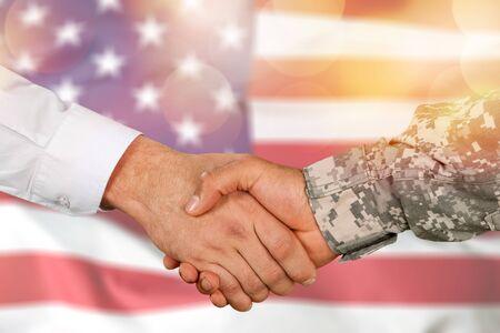 Amerikanischer Soldat im Uniform- und Zivilmannhandschlag Standard-Bild