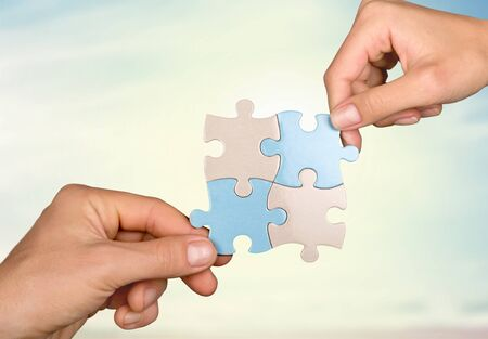 Human hands joining puzzle parts on background