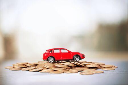 Monedas de oro y coche de juguete en el fondo