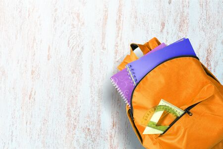 Flat lay composition with backpack, school stationery and space for text on light background Stockfoto