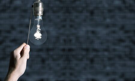 Mano apagando la bombilla de la lámpara. Apagando la luz. Foto de archivo