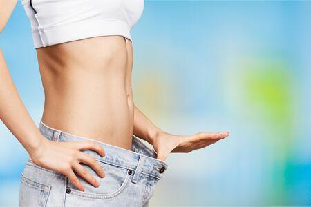 Junge Frau, die Taille zeigt. Konzept zur Gewichtsabnahme