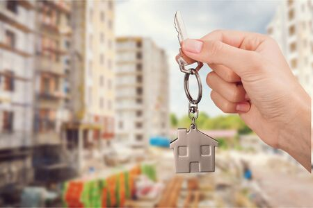 Home key in house keychain on woman man human hand support offering security protection awareness concept: Insurance agent in white shirt holding happy residential key lock unlock Stockfoto