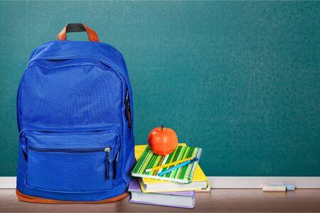 Blauer Schulrucksack im Hintergrund.