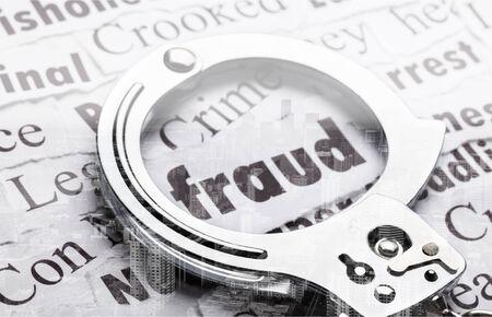 Handschellen auf Papieren mit Worten, Betrug in Standard-Bild