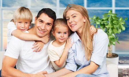 Bella famiglia sorridente seduta al divano su