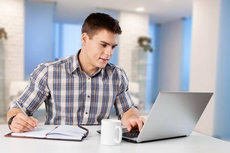 Il giovane felice lavora sul suo computer portatile