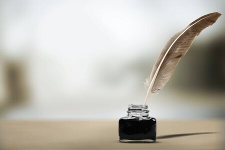 Quill pen with inkwell on wooden desk.
