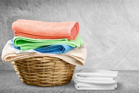 Laundry Basket with colorful towels on background