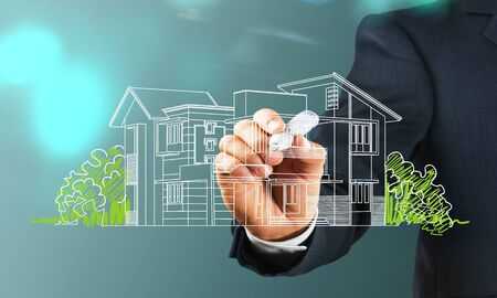 Business man drawing a house on background Stockfoto