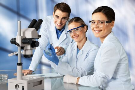 Female and male scientists in glasses working with microscope Banco de Imagens
