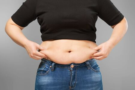 diet, dieting, Overweight lady holding stomach Archivio Fotografico - 131984264
