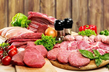 Fondo de carne cruda fresca con verduras en un escritorio de madera aislado sobre fondo blanco. Foto de archivo