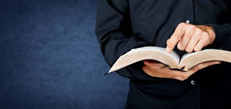 Man hands holding open book on black background