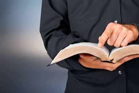 Hombre leyendo viejo libro pesado sobre fondo