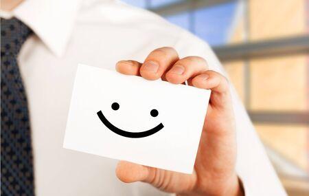 Mann, der eine Visitenkarte mit glücklichem smiley hält Standard-Bild