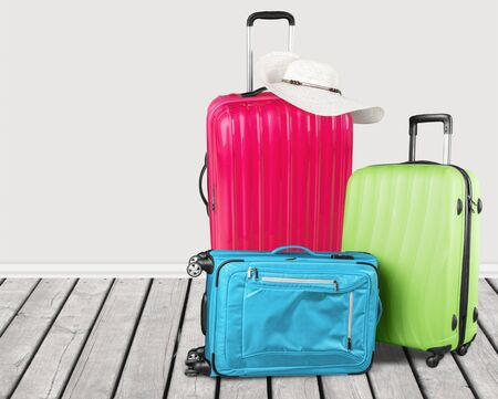 Colorful suitcases stack on wooden background