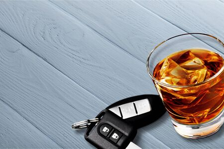 Glass of whiskey and car key on wooden background