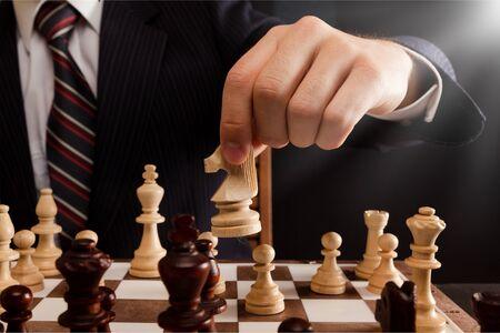 Biznesmen ręka trzymająca pionek szachowy na szachownicy