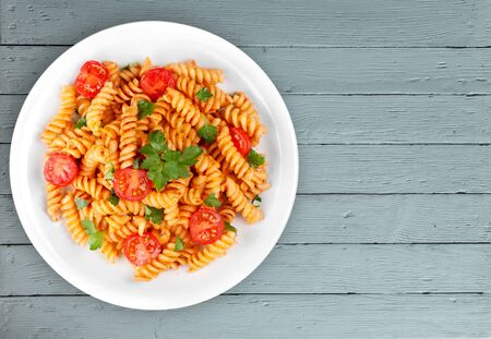 Pasta fusilli with bolognese tomato beef sauce on the kitchen table