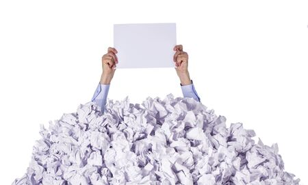 Person unter zerknittertem Papierstapel mit Händen, die eine leere Seite halten holding