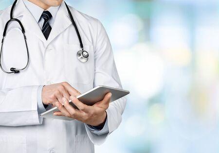 Medico del primo piano all'ospedale che lavora con il pc della compressa