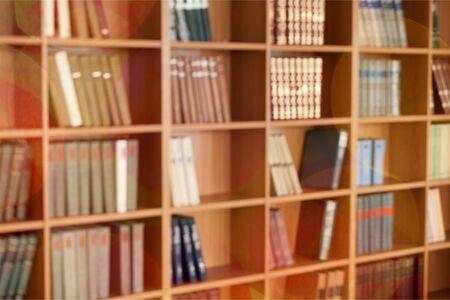 Molti libri sugli scaffali, sfondo sfocato della biblioteca
