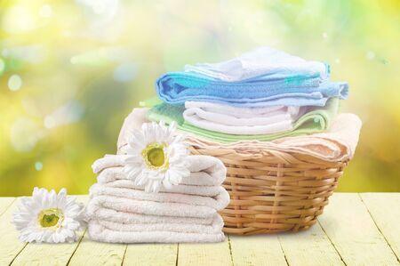 Panier à linge avec des serviettes colorées sur fond