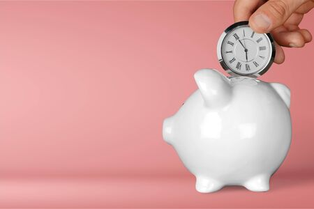 Hand depositing clock in piggy bank