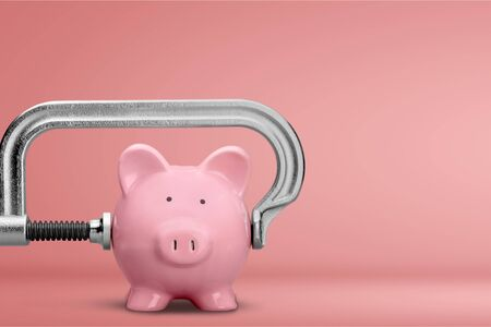Pink piggy bank and clamp on background Stockfoto