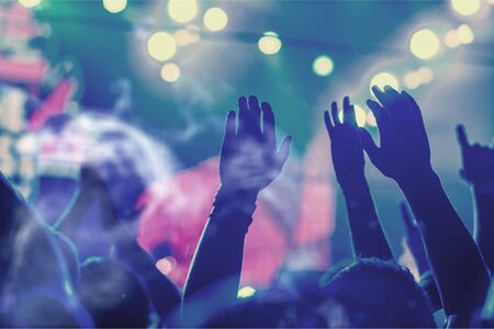 Audiencia con manos levantadas ante una música Foto de archivo
