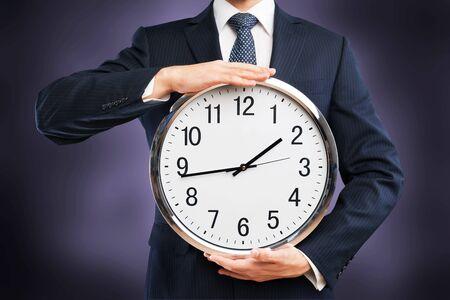 Image of businessman holding clock Stockfoto - 129161297