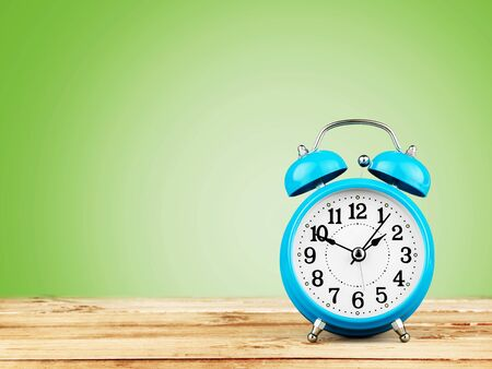 Despertador retro azul sobre mesa de madera
