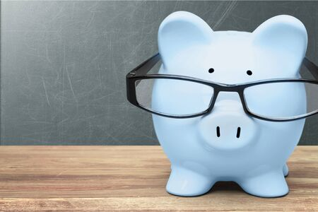 Blue piggy bank in glasses on background Stockfoto