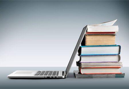 Pila di libri con il computer portatile sul tavolo