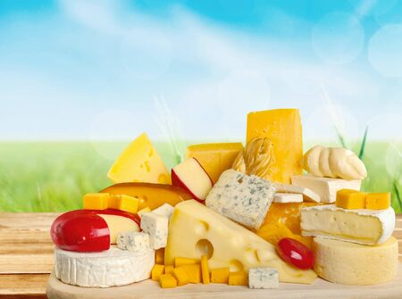 Heap of assorted cheese with spices on light background