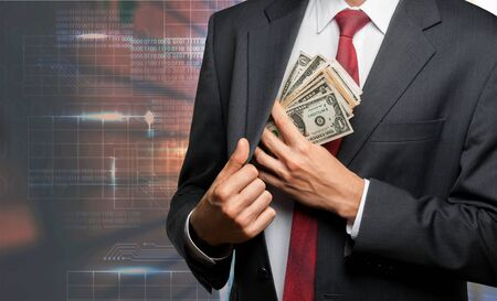 Businessman hiding dollars banknotes in the pocket of jacket