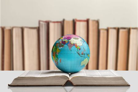 Heavy book and globe on background