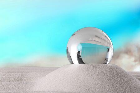 Closeup of glass earth globe on the sand
