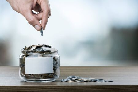 Hand putting Coins in glass jar