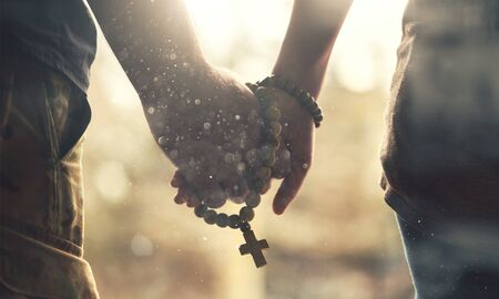 Couple praying together. Holding rosary in hand. Stock Photo - 129756854