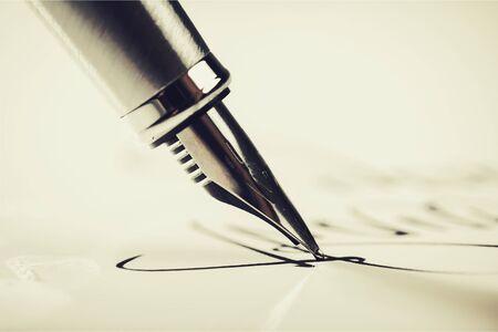 Een handtekening ondertekenen met een vulpen Stockfoto