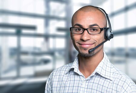 Portrait of a smiling man with headset working as a call center operator