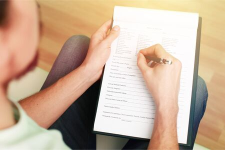 Hand writing in clipboard form psychologist filling clipboard session blank