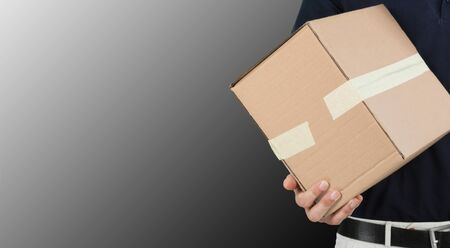 Hands of delivery man holding package