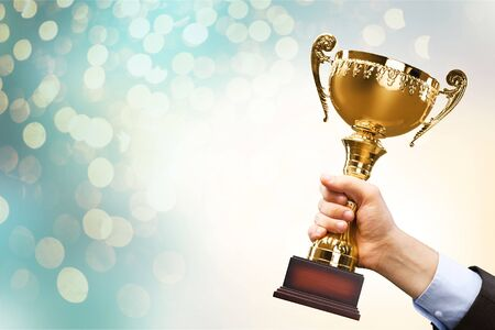 Close-up human hand holding golden Trophy on blurred background Stock Photo