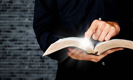 Young man hands holding open book