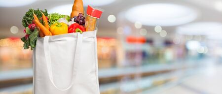 Eco friendly reusable shopping bag filled with vegetables on a blur background